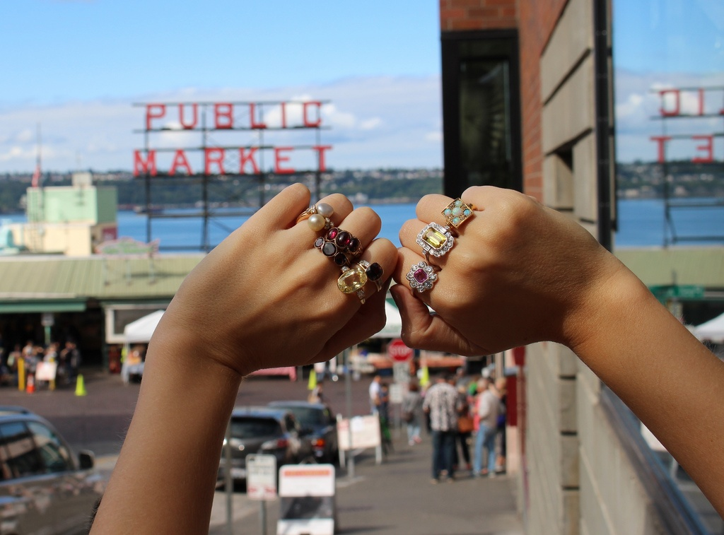 Several rings on both hands with public market in background