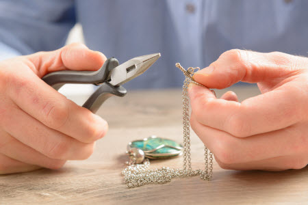 Jeweler fixing jewelry that's about to break.