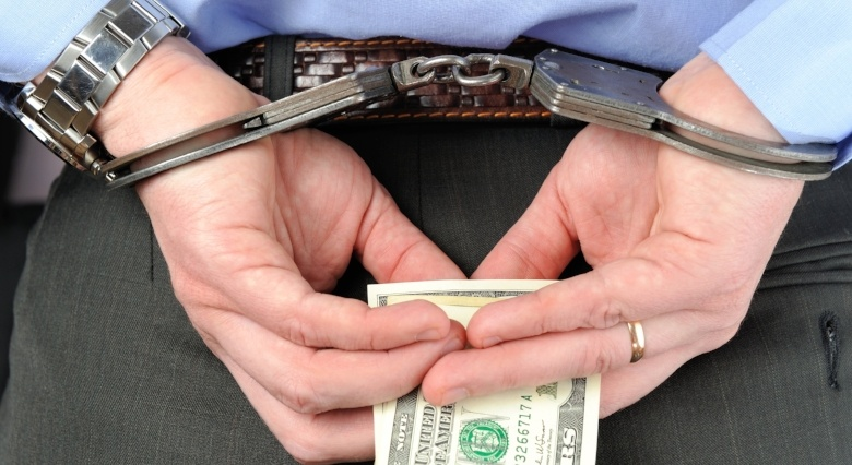 Handcuffed and holding money